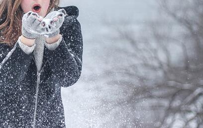 Image of a woman blowing snow out of her hands