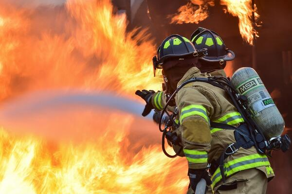 Image of two firefighters fighting a fire