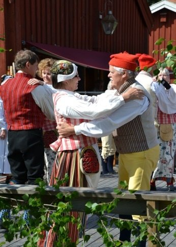 An image of Swedes celebrating Midsommar in traditional attire.
