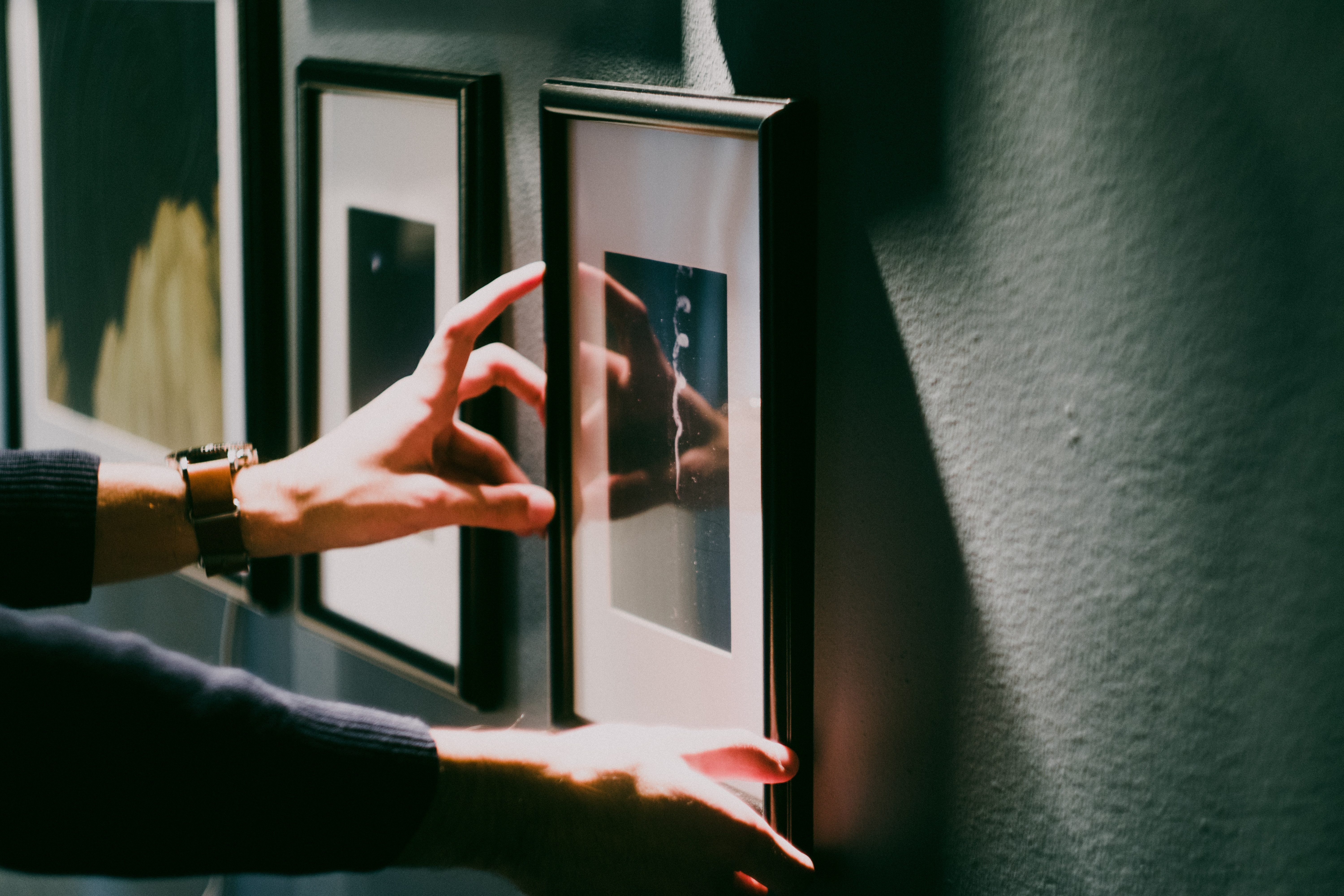 Image of a person hanging a picture in a temporary housing apartment