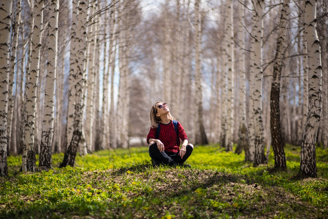 Image of a young lady sitting in the forest