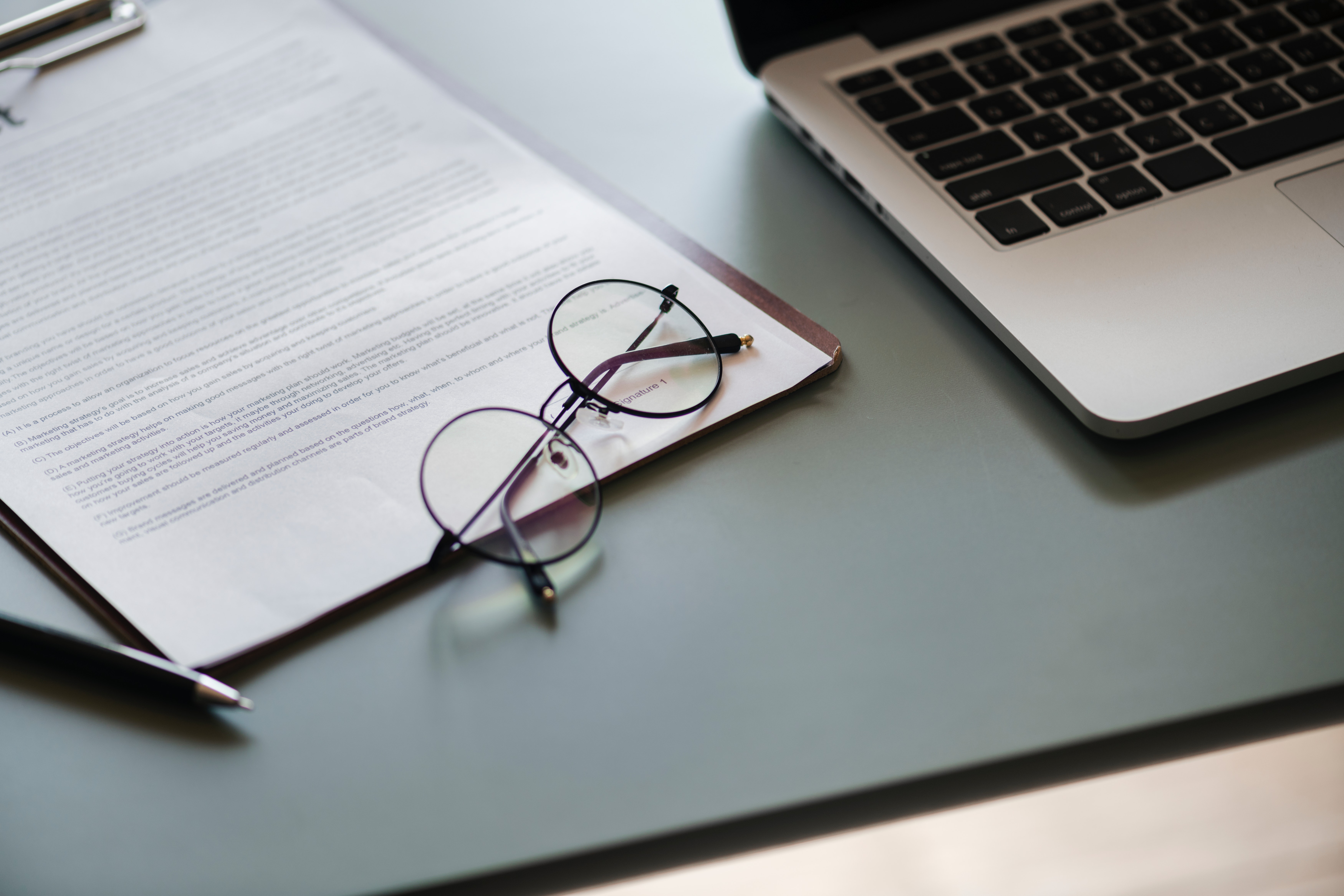 photo of a laptop, a pair of glasses, and a contract on a table