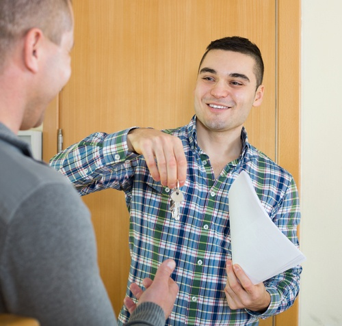 Image of a happy tenant receiving keys from a landlord