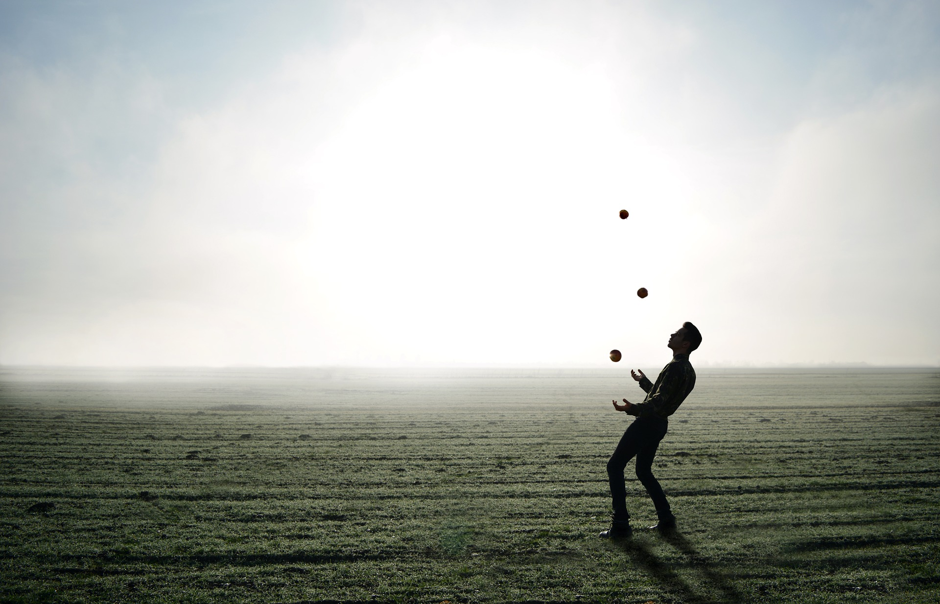 Image of a man juggling on a beach